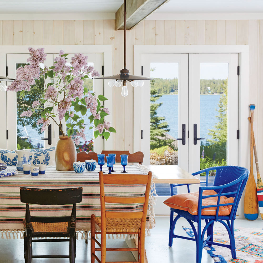 beach house dining rooms coastal living blue wicker end chair wooden walls lake view round metal glynn accent table white and gold lamp reclaimed silver cocktail mats coasters