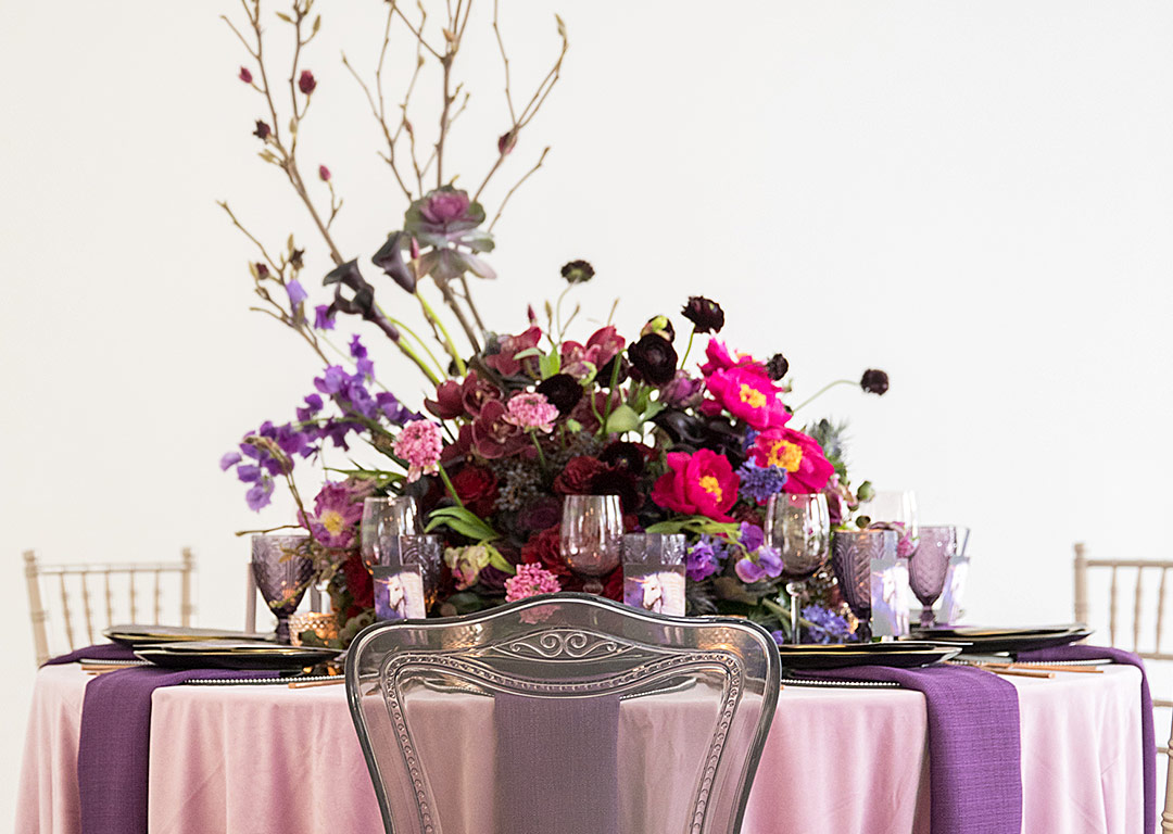 magical styled shoot with unicorns and shades purple nuage fantasy wedding black color palette unicorn magic event ideas accent table clear glassware gold edge mirrored chargers