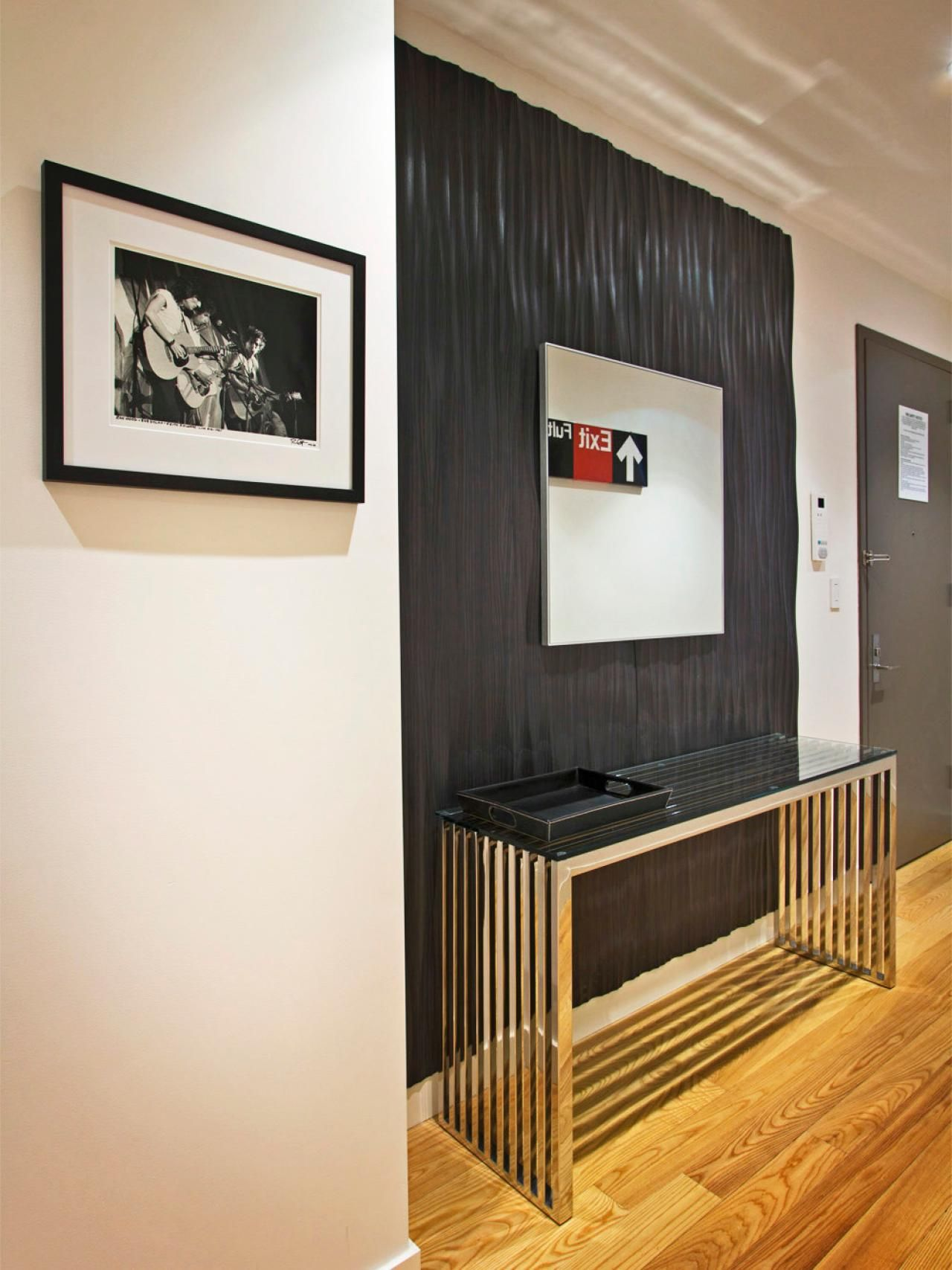 this contemporary entryway features textured ebony accent wall foyer table featuring modern artwork that provides stark contrast against the otherwise white walls ikea small and