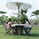two young women sitting table under umbrella side view stock ture outdoor adjustable drum throne round concrete teal bedroom chair small metal accent couch plans moroccan lamp 150x150