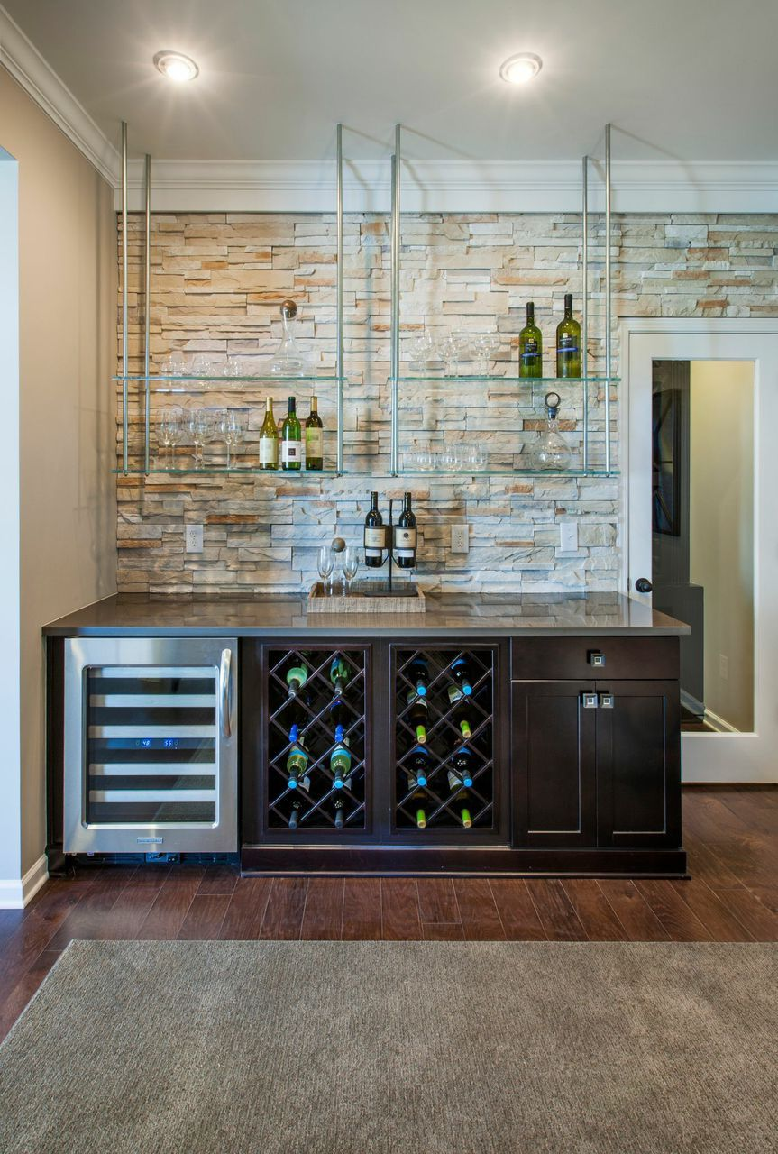 create dynamic home bar with floating glass shelves that contrast lights the light stone accent wall and dark wood cabinets seen waterstone raleigh large kitchen cart black