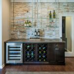 create dynamic home bar with floating glass shelves that contrast the light stone accent wall and dark wood cabinets seen waterstone raleigh white for shoes shelving units small 150x150