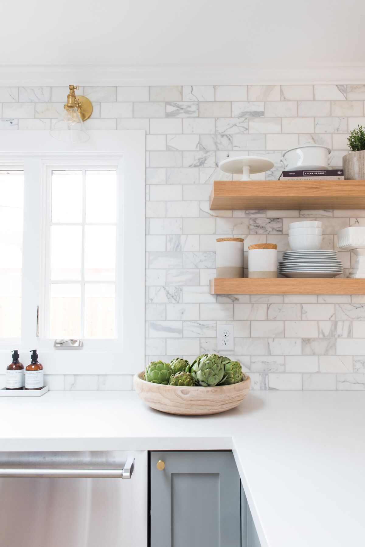 emerson project webisode reveal design inspo marble subway tiles white floating shelf pale grey cabinets tile brass sconces shelves wood shelving units countertop supports
